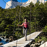 """Hike across a swing bridge beneath The Horns (Los Cuernos) in the the French Valley (Valle Frances) in Torres del Paine National Park, Chile. """"The Horns"""" (about 6900 feet or 2100 meters elevation) are a pinkish-white granodiorite intrusion formed 12 million years ago topped with an older crumbly dark sedimentary rock, exposed by freeze-thaw erosion and glaciation. The foot of South America is known as Patagonia, a name derived from coastal giants, Patagão or Patagoni, who were reported by Magellan's 1520s voyage circumnavigating the world and were actually Tehuelche native people who averaged 25 cm (or 10 inches) taller than the Spaniards. For licensing options, please inquire."""