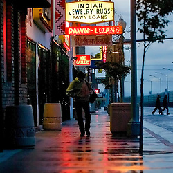 061107    Brian Leddy.Pedestrians make their way to their destination on Historic Route 66 on Monday during a light rain shower. Scattered thunderstorms are expected to continue thru Tuesday..