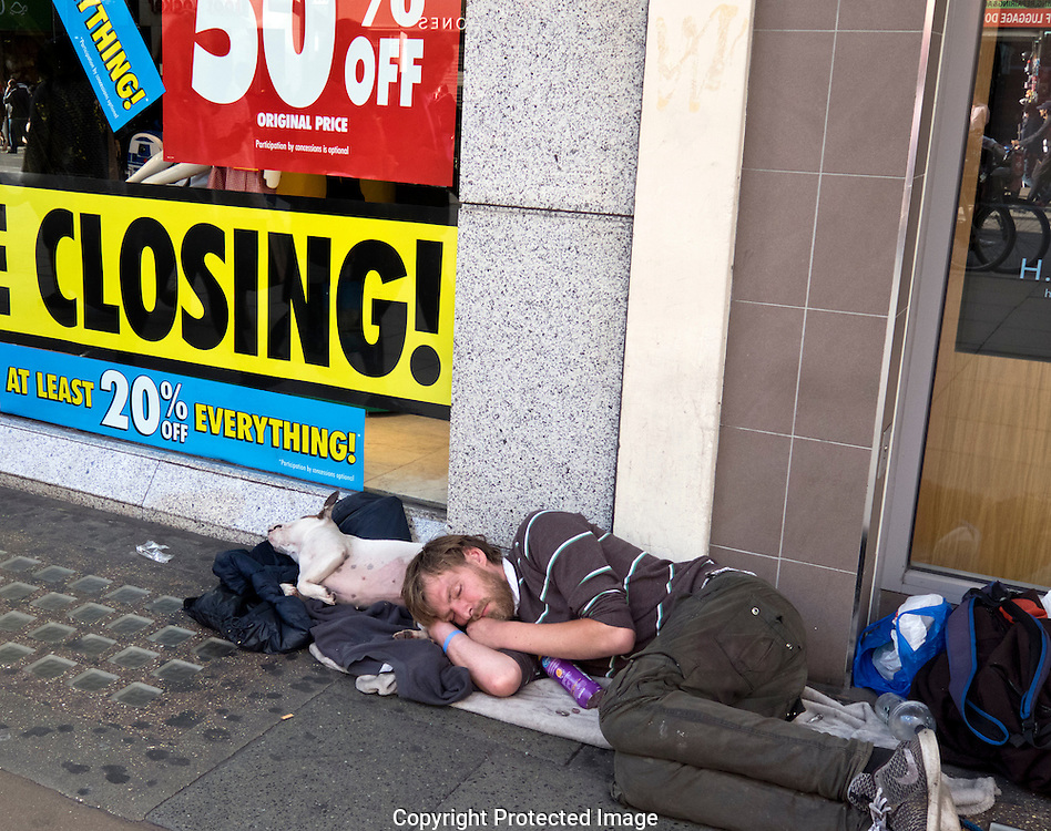 Homeless man sleeping outside the closing down sale of british Home Stores in Oxford Street London