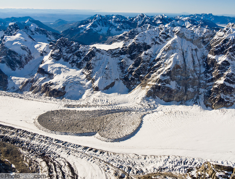 Heart shaped avalanche debris rides a glacier in the Alaska Range, USA. Flightsee over Denali National Park and Preserve to see a vast wilderness of glaciers, icy peaks, and mile deep granite gorges.