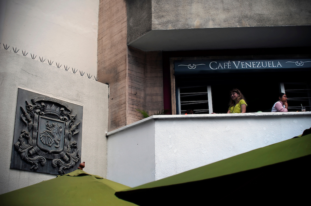 "A woman drinks coffee on the balcony of Cafe Venezuela in Caracas. Cafe Venezuela is a chain of coffee shops run by Hugo Chavez's socialist government that serves locally grown coffee and traditional Venezuelan food, all sold at discounted, ""socialist"" prices. This particular location, in Plaza Bolivar, was a shoe store before Chavez nationalized the building and turned it into Cafe Venezuela."