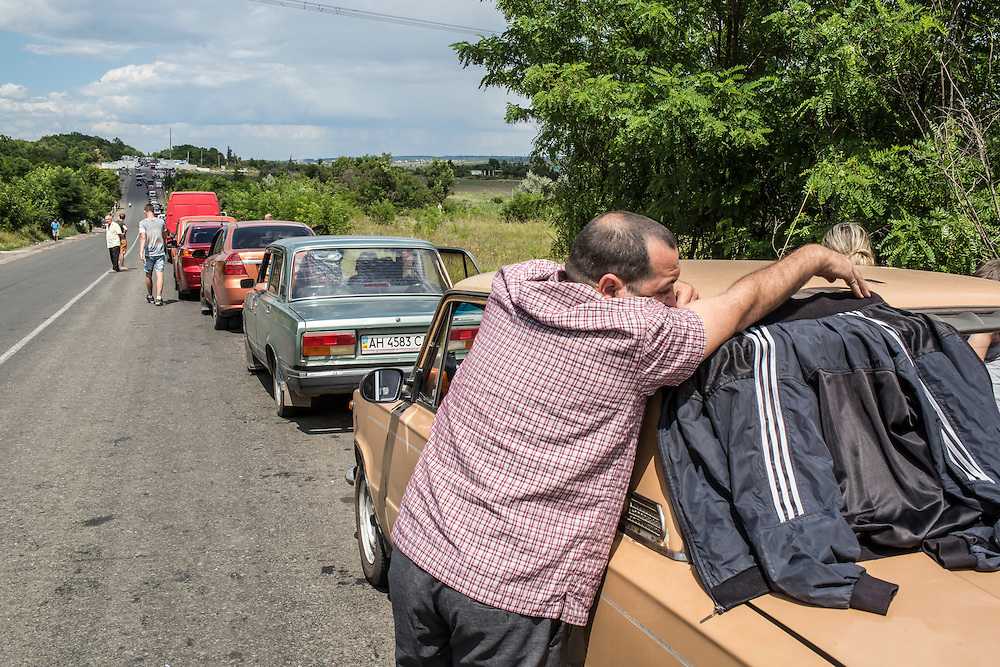 ZAITSEVE, UKRAINE - JULY 9, 2016: A man waits in a long line to cross from the rebel-held Donestk People's Republic to Ukrainian government-controlled territory at a checkpoint in Zaitseve, Ukraine. The wait can stretch hours, or sometimes even days. CREDIT: Brendan Hoffman for The New York Times