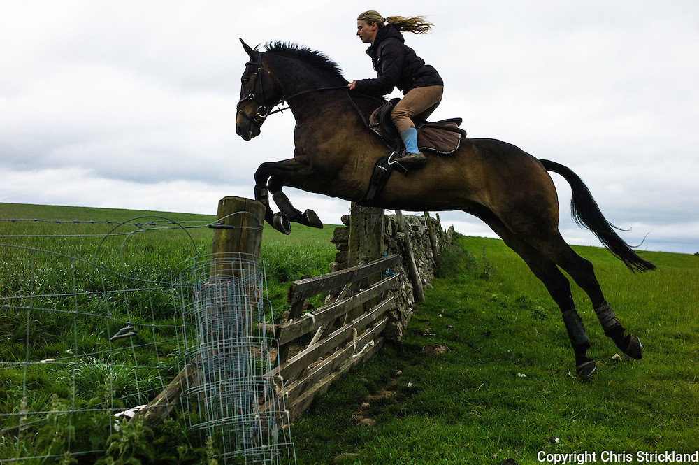 Ancrum, Jedburgh, Scotland, UK. 19th June 2015. Four Star eventer Emily Galbraith jumps a gate while exercising eventer 'Johnny' in the Scottish Borders.
