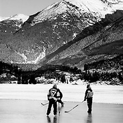 Skaters play hockey on frozen Green Lake.  Whistler BC, Canada