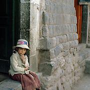 Girl sitting at doorway between Inca walls in Cuzco, Peru