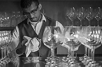 Busser Akram Buhary polishes wine glasses at the Farmhouse Inn in Sonoma County.