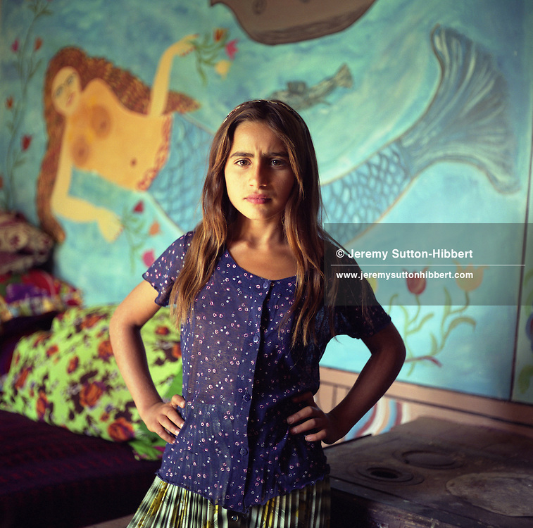 Mia, a young Roma girl stands in front of a mermaid painted on the wall of a Roma home, in the old part of the Roma camp of Sintesti. Mermaids are very popular as wall decoration, but no-one within the camp knows the reason why they were first painted..