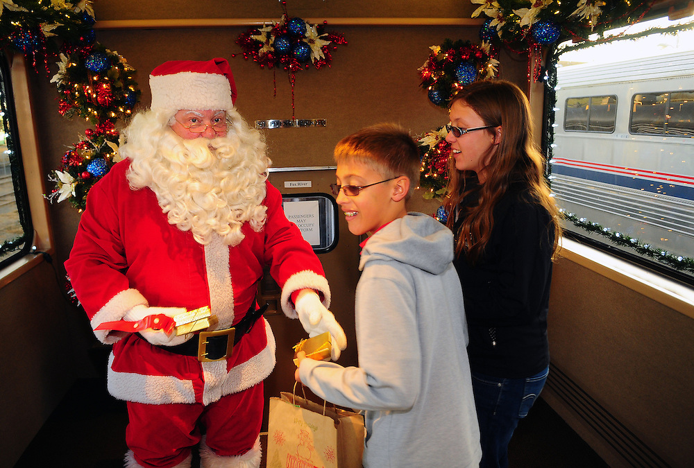 """Santa presents gifts to 12-year-old Andrew Wormley, and his 14 year-old sister Alex, while on board the BNSF Railway """"Holiday Express"""" on Tuesday  December 4, 2012. The railway company offered 300 military families a 90-minute ride on the the specially decorated train.   (Adolphe Pierre-Louis/Journal)"""