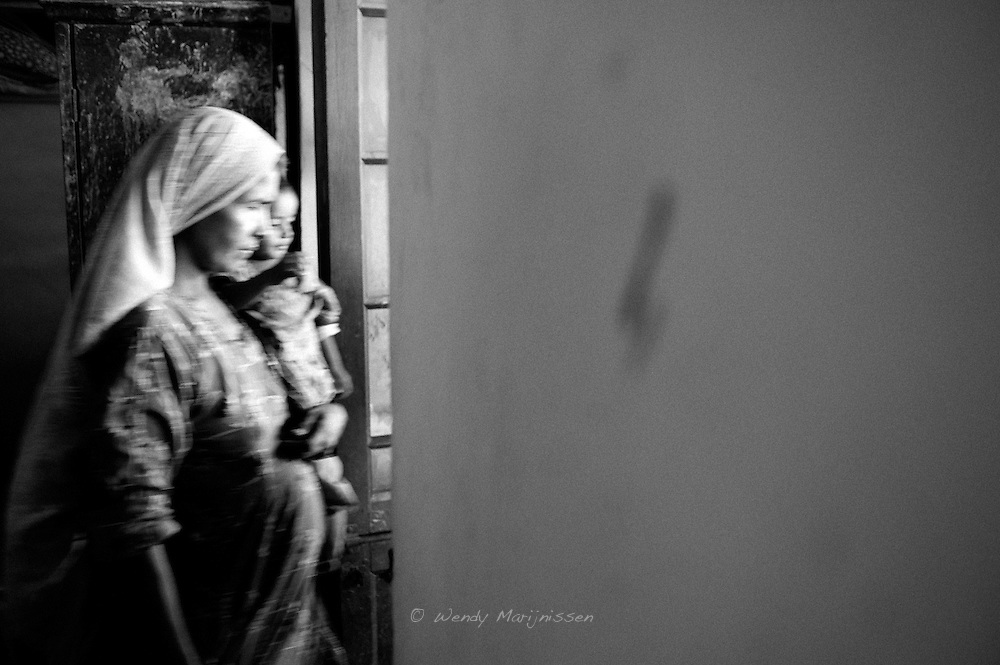 A pregnant woman and her child leave the makeshift doctors office in a school now housing IDP's affected by the floods. Providing antenatal care is one of the priorities for doctors assisting the flood victims. Shikarpur, Pakistan, 2010