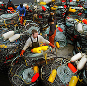 Crab pots are being readied and stacked as another boat is prepped for fishing.