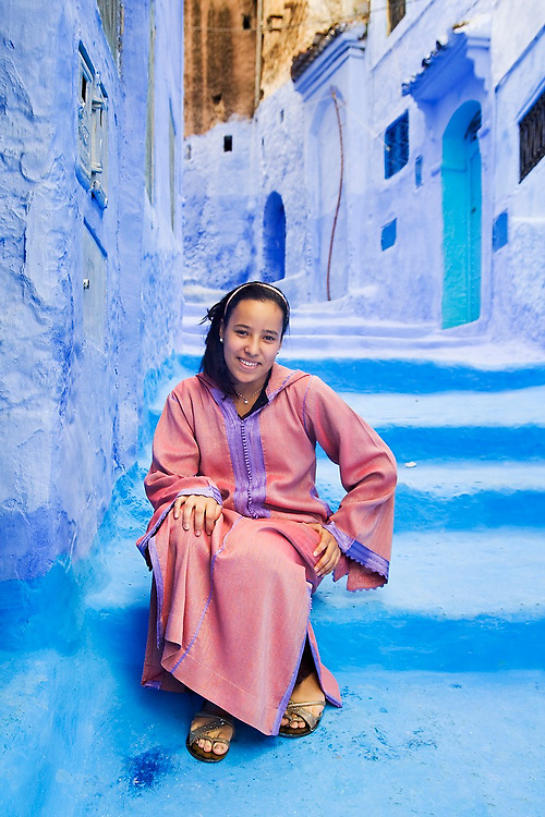 A young woman in a pink djellaba poses for a portrait in a narrow blue alley, Chefchaouen medina, Morocco.