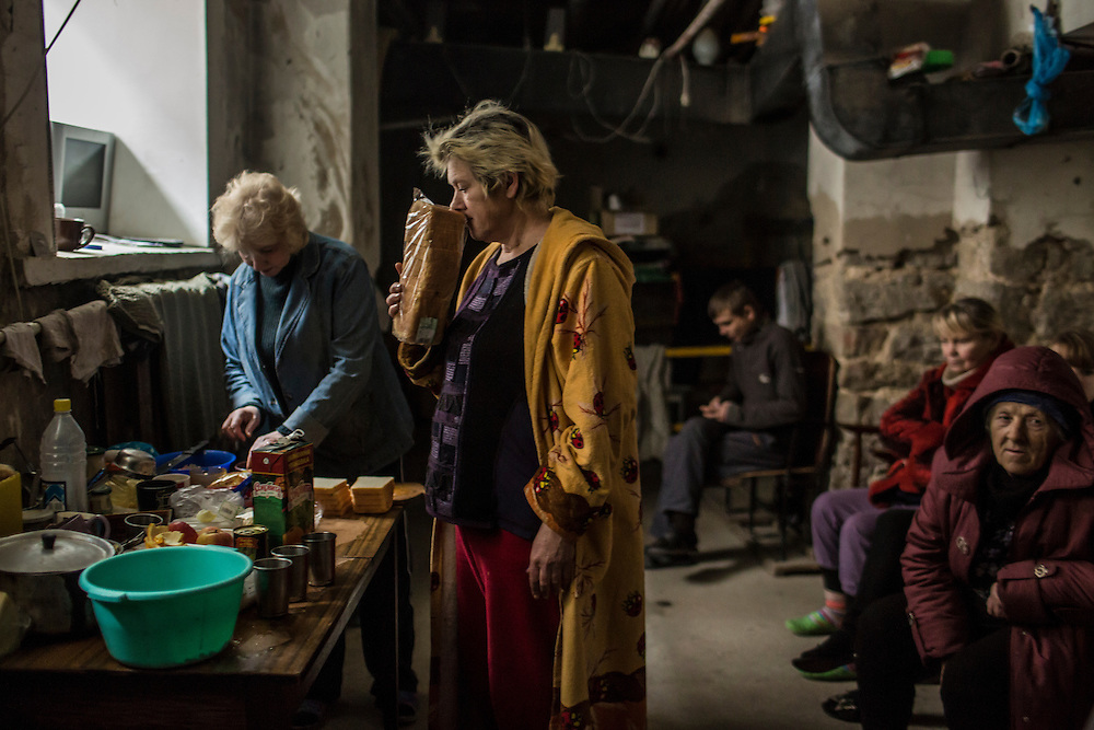 DONETSK, UKRAINE - JANUARY 29, 2015: Local residents prepare lunch in the dark during a power outage in an underground bomb shelter in the Petrovskyi district of Donetsk, Ukraine. The neighborhood has been shelled heavily in the past few days, forcing many people back to the shelters they first fled to in the summer. CREDIT: Brendan Hoffman for The New York Times