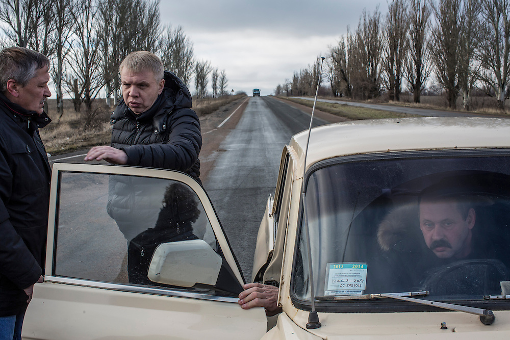 OLENIVKA, UKRAINE - FEBRUARY 3, 2015: Residents of the village of Olenivka wait along the side of the road at the edge of town for audible shelling to diminish so they can return home in Olenivka, Ukraine. As fighting between Ukrainian and rebel forces remains fierce, rebels today claimed that they downed both a helicopter and an airplane belonging to Ukrainian forces over the past 24 hours. CREDIT: Brendan Hoffman for The New York Times