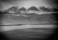 The glaciers of Kangur Shan, in Chinese Tukestan's Pamir Mountains, tumble from over 7,700 meters onto a treeless high desert inhabited by Kyrgyz herdsmen at 3,600 meters and eventually feed the fertile oases of the Taklamakan Desert far below where the Turkic Uighur people and Indo-European inhabitants before them have lived for over 3,000 years.  The valley was once filled by the glaciers and the Taklamakan Desert was once a steppe grassland.