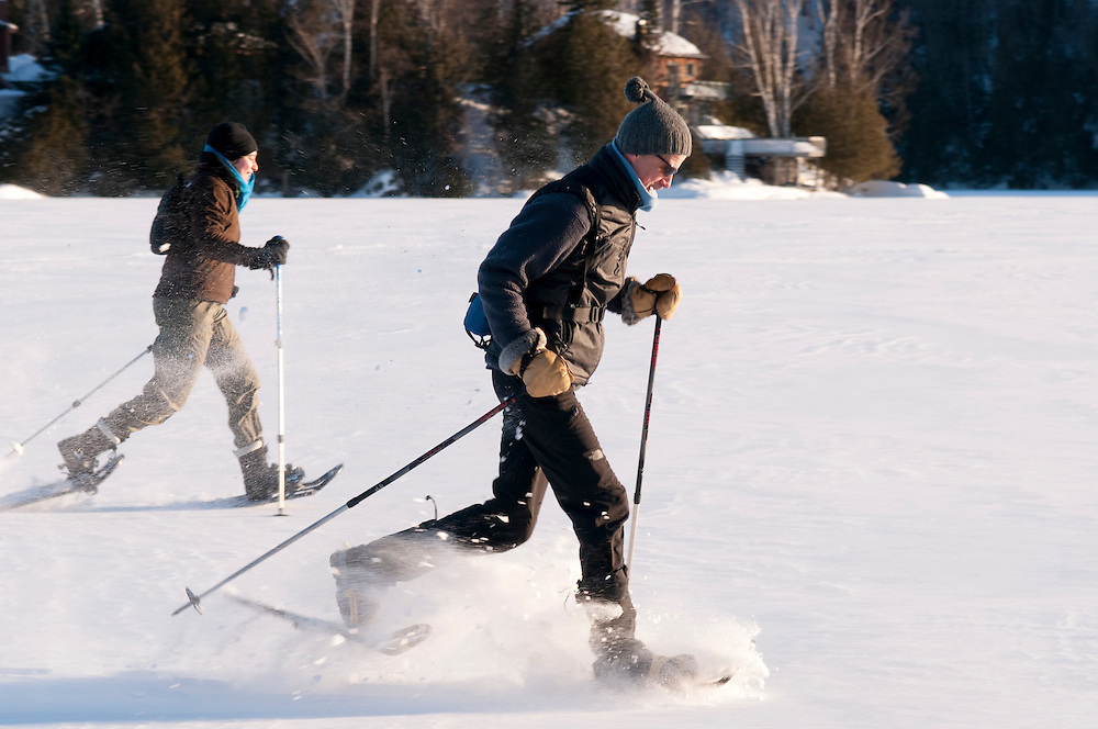 a couple having fun  running on lake with snowshoes.