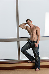 shirtless muscular lean man leaning against a large window at home