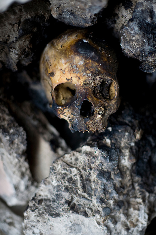 A human skull and rubble sit in a partially collapsed building.