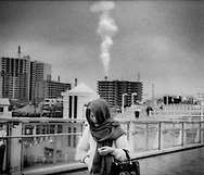 Woman rushes home in a light rain while stack issues a plume into Kawasaki sky, Japan.  Kawasaki is from where Japan's post-war economic might came.  Now, as much of Japan's heavy industry has been moved off shore, mostly to China and exports decreased by 46% in January 2009, this export-driven economy has begun the process of serious soul searching.  The current economic malaise has intensified pressure on Japan's blue collar and contract workers.  Where to from here for Japan, Inc.?