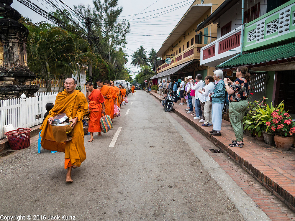 "12 MARCH 2016 - LUANG PRABANG, LAOS: Tourists watch Buddhist monks during the morning tak bat in Luang Prabang. Luang Prabang was named a UNESCO World Heritage Site in 1995. The move saved the city's colonial architecture but the explosion of mass tourism has taken a toll on the city's soul. According to one recent study, a small plot of land that sold for $8,000 three years ago now goes for $120,000. Many longtime residents are selling their homes and moving to small developments around the city. The old homes are then converted to guesthouses, restaurants and spas. The city is famous for the morning ""tak bat,"" or monks' morning alms rounds. Every morning hundreds of Buddhist monks come out before dawn and walk in a silent procession through the city accepting alms from residents. Now, most of the people presenting alms to the monks are tourists, since so many Lao people have moved outside of the city center. About 50,000 people are thought to live in the Luang Prabang area, the city received more than 530,000 tourists in 2014.       PHOTO BY JACK KURTZ"