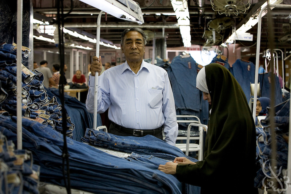 Air Marshal Man Mohan Sinha, chairman of Velocity Apparelz CO looks over one of his factory production lines October 27, 2008 on the production floor at the Velocity factory in Ismailia (130 kilometers north of Cairo, Egypt.)  Sinha and his son Siddharth, CEO of the parent company Vogue International Agencies FZE are Indian businessmen who have been operating their jeans company in Egypt since 2001, employing 2700 Egyptian workers while supplying jeans to major companies that include Levis, Target, and Zara.