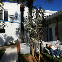 ST. PETE BEACH, FL -- February 13, 2010 -- Andres Ruales and his wife, Beth, of Orlando, spend part of their weekend trip lounging in a hammock outside of their room at the Postcard Inn in St. Pete Beach, Fla., on Saturday, February 13, 2010.  The beachfront U-shaped hotel, originally built in 1957, was renovated into a throwback surf shack of sorts with rooms featuring surfing imagery and vintage furniture. (Chip Litherland for The New York Times)