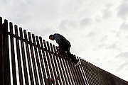 Migrants climb a border fence into the United States from Mexicali, Mexico on Friday, April 14, 2006.<br />