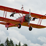 Wing flyers do a low pass on a Stearman biplane at the Air Affaire flying festival in Sequim, WA. Mike and Marilyn Mason teach wing walking and flying locally here. http://www.westcoastspindoctors.com/wing_walking.html
