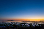 Looking down on the tidal flats at low tide in Dungeness bay, inside 5 mile long Dungeness Spit. The Dungeness Lighthouse can be seen, along with Mt. Baker (60 miles away or so across the Strait of Juan de Fuca) emerging from the marine layer in the pre-dawn. Sequim WA