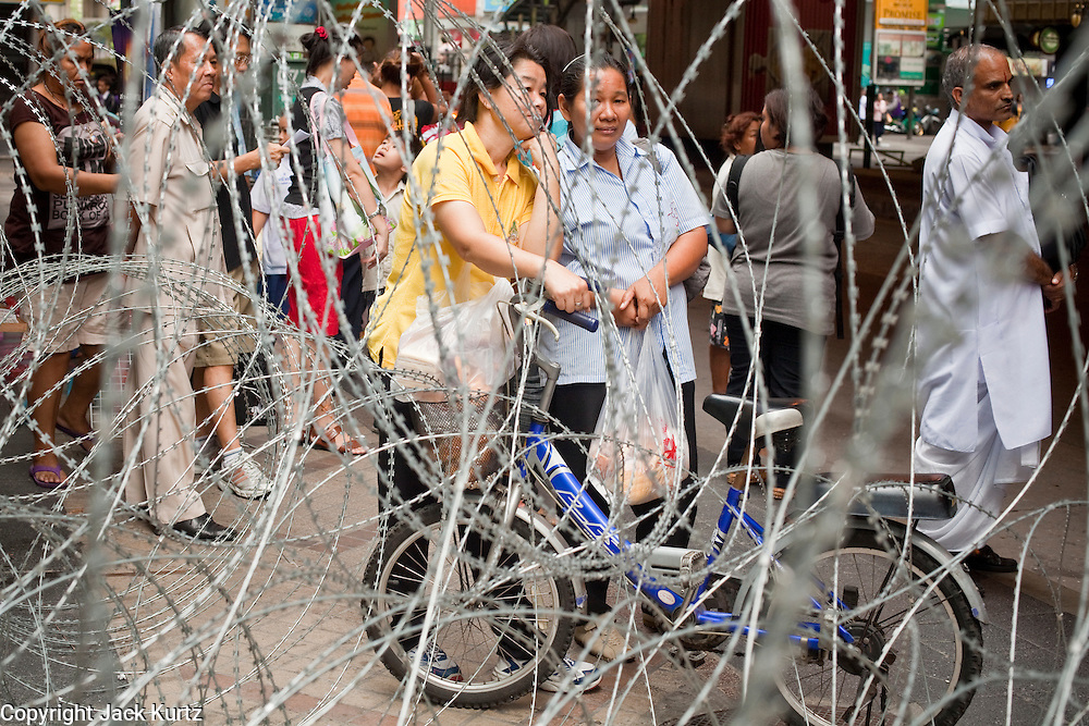 "May 12 - BANGKOK, THAILAND: People wait at a bus stop ringed with razor wire on Silom Road near the front line of the army and Red Shirt protesters Wednesday morning. The Thai government said Wednesday that time has run out for ""Red Shirt"" protesters in Ratchaprasong and Sala Daeng Intersections in Bangkok and that a crackdown could come at any time. As news of the anticipated crackdown spread, Red Shirt protesters continued with an almost festive mood at their main stage but many of the sleeping areas around the protest site appeared to be empty. No official estimates on crowd size are available.  Photo by Jack Kurtz"