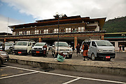 BU00002-00...BHUTAN - Tour guides and drivers, wearing the Ghos, (the national dress), picking up clients at the Paro International Airpoirt.