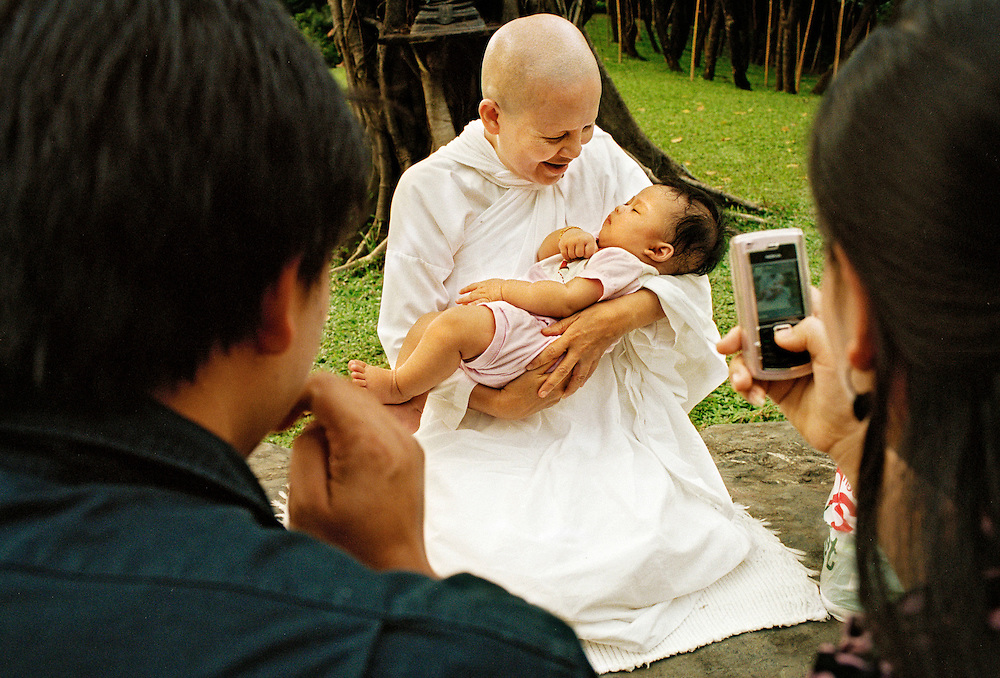A couple photographs when Mae Chee Sansanee holds their baby.   Mae Chee Sansanee is known all over Thailand for her good hand with children, especially since national TV broadcasts her regular playing sessions with the kings grandson. ..Photographer: Elin Berge / MOMENT