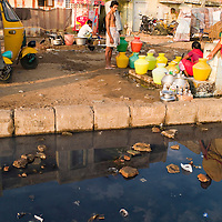 Ladies collect water, their reflections in the waste water. Santhome Beach and adjoining Marina Beach in Chennai, India were hit hard by the 2004 Tsunami. Fishermen and their families were the main victims living in their lightweight huts on the long and flat beaches of the area. All structures within 300 metres of the sea have now been banned and any left standing after the Tsunami were demolished. The fishermen and their families have now been relocated to government blocks of flats which has become a Santhome slum for fishermen and their families.