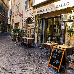 "An old cobbled street in the heart of Rome with its traditional ""Osteria"" type restaurants"