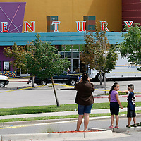 """People take pictures as police continue to investigate at the Century movie theater where 12 people were shot last Friday as a showing of """"Batman"""" in Aurora, Colorado July 23, 2012. REUTERS/Rick Wilking (UNITED STATES)"""