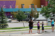 "People take pictures as police continue to investigate at the Century movie theater where 12 people were shot last Friday as a showing of ""Batman"" in Aurora, Colorado July 23, 2012. REUTERS/Rick Wilking (UNITED STATES)"