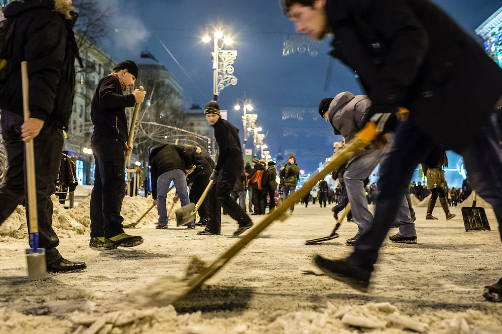 KIEV, UKRAINE - DECEMBER 11: Anti-government protesters clear snow from the streets near Independence Square on December 11, 2013 in Kiev, Ukraine. Thousands of people have been protesting against the government since a decision by Ukrainian president Viktor Yanukovych to suspend a trade and partnership agreement with the European Union in favor of incentives from Russia. (Photo by Brendan Hoffman/Getty Images) *** Local Caption ***