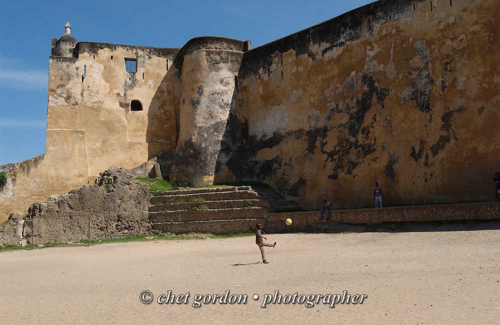 A boy kicks a soccer ball on the grounds of Fort Jesus in the Old Town neighborhood of Mombasa, Kenya on Friday, April 14, 2006.