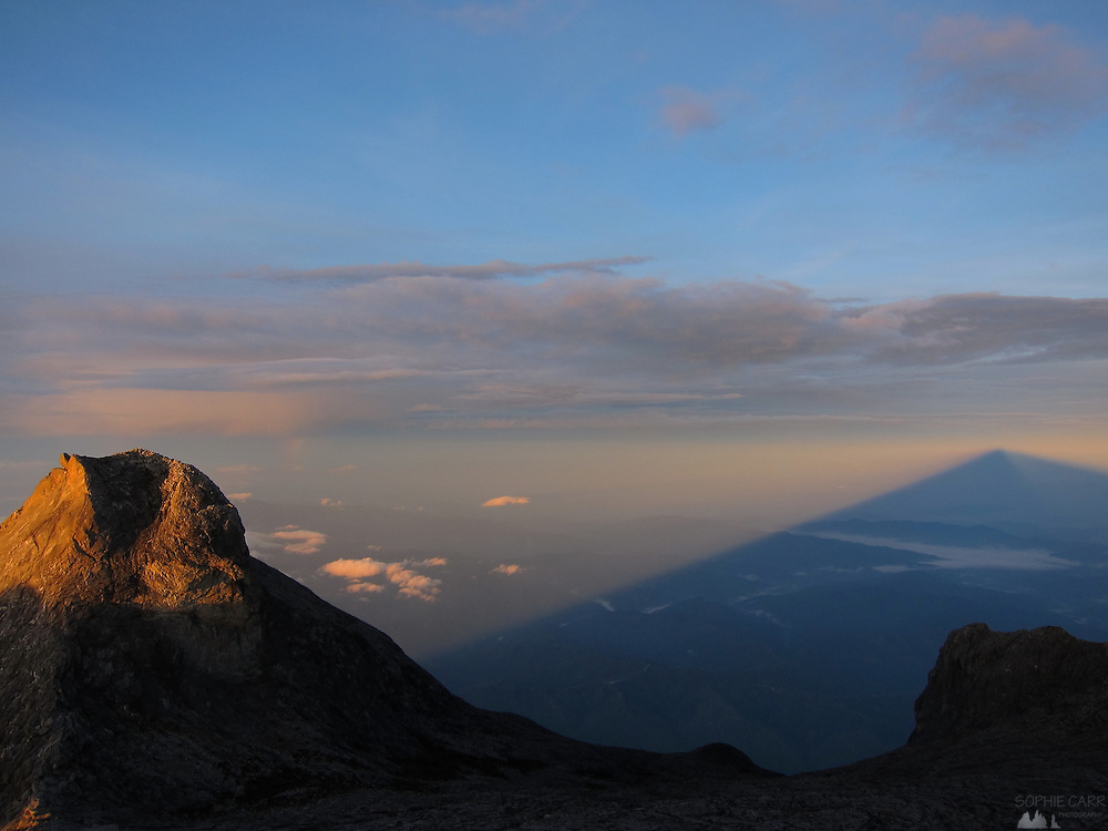 It is normal to climb to Low's Peak on Borneo's Mt. Kinabalu in the early hours of the morning to reach the peak for sunrise. Just after the sun comes up there is a perfectly triangular mountain shadow, a phenomenon seen on many high, free-standing mountains around the world