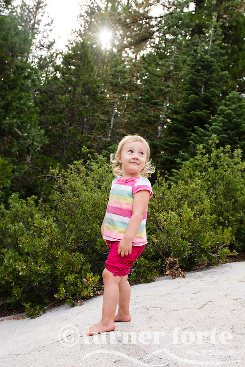Portrait of smiling toddler girl standing on large rock with sunburst through woods in background near Strawberry, California.