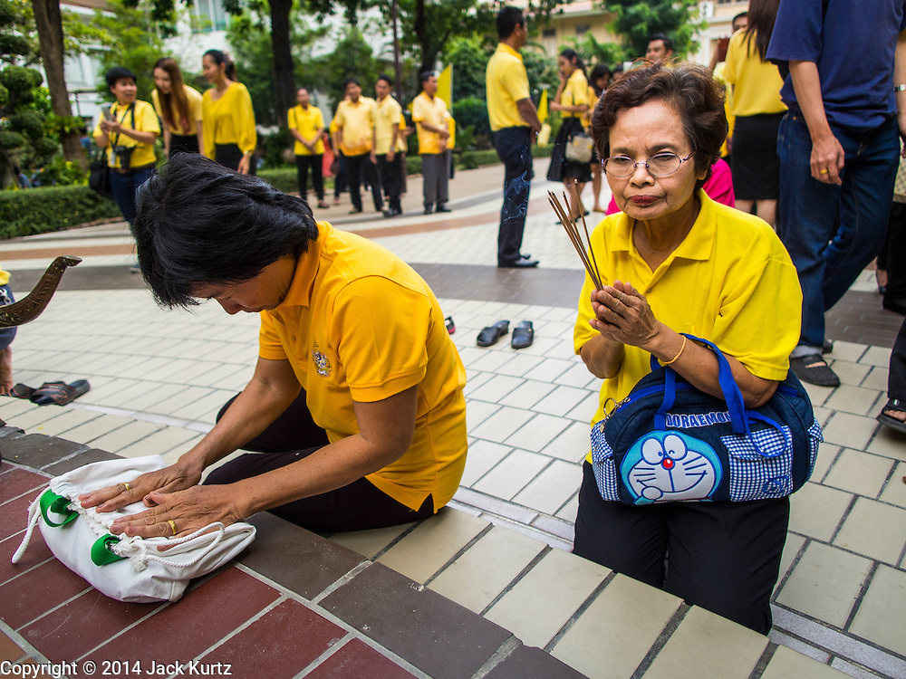 28 NOVEMBER 2014 - BANGKOK, THAILAND: Women on the plaza in front of Siriraj Hospital pray for Bhumibol Adulyadej, the King of Thailand. The King was born on December 5, 1927, in Cambridge, Massachusetts. The family was in the United States because his father, Prince Mahidol, was studying Public Health at Harvard University. He has reigned since 1946 and is the world's currently reigning longest serving monarch and the longest serving monarch in Thai history. Bhumibol, who is in poor health, is revered by the Thai people. His birthday is a national holiday and is also celebrated as Father's Day. He is currently hospitalized in Siriraj Hospital, recovering from a series of health setbacks. Thousands of people come to the hospital every day to sign get well cards for the King. People wear yellow at events associated with the King because he was born on a Monday, and yellow is Monday's color in Thai culture. It's also the color of the monarchy.       PHOTO BY JACK KURTZ