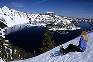 Snowshoer takes a break overlooking Crater Lake, Wizard island seen from the rim near man lodge.