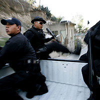 Tijuana Police agents in route to a neighborhood to search for illegal contraband during a drug sweep in Colonia Chula Vista  in Tijuana, Mexico.  Since  the introduction of Operation Gatekeeper and the events of 9/11, security along the border has tightened along border cities such as San Diego, El Paso and other large cities causing migrants to cross from Mexico into the United States in more remote areas.  As a result, an ever increasing number of deaths have been reported and commerce has been severely affected.  2006 was also the year hundreds of thousand Latinos took to the streets across the United States in an effort to show Congress and the President how vital they are to America.