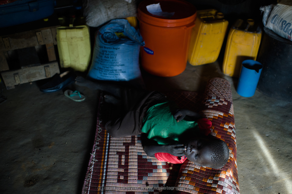 Albino Simon, one of Simon Jackson's eight children, rests on a mat as his mother cooks dinner at their home in the village of Kudo in Eastern Equatoria in South Sudan on 8 August 2014.