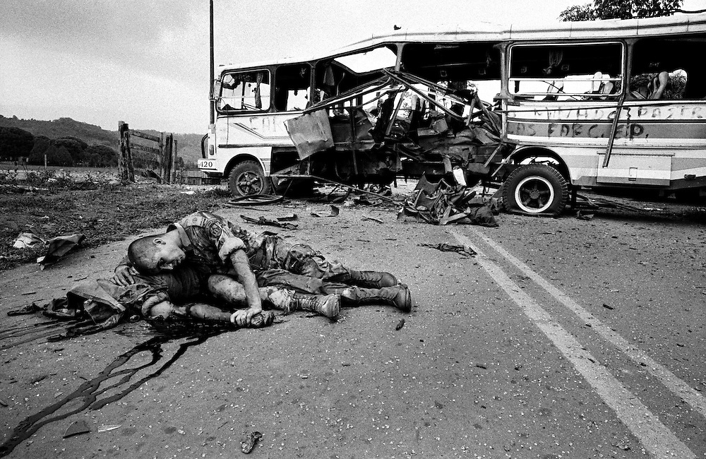A wounded Government soldier lies alongside his dead companion moments after a FARC planted bomb exploded in a bus used as a roadblock. The highway had been cut on the 23rd of February and  Ingrid Betancourt was kidnapped when her vehicle was stopped at the obstruction.