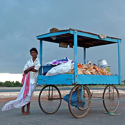 """A man waits to sell food to fishing families from New beach in Nagapattinum district in Tamil Nadu, India get as they take part in the unique ritual of reliving the day when Athi Baktha Nayanar found a gold fish in the ocean, offered it to his God and received """"moksha"""", September 2,2005. Villagers worship this God who is know to be the God of the Sea and the 49th nayanmar. The yearly ritual symbolizes an unwavering  pious man who always offered his daily catch to his God first, even when people in his village were starving. The ritual had been stopped for 25 years and many fishermen believed this is why the tsunami ravaged the coast of India.  (Ami Vitale)"""