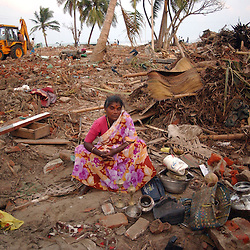 A survivor of the tsunamis that ravaged the coast of India and Asia sits where her house once stood with all that she could salvage from the wreckage January 5, 2005 in Nagapattinum in the state of Tamil Nadu. The official death toll in India  has reached about 15,000 people and the total dead is over 150,000 in the 11 nations that were hit. (Ami Vitale)