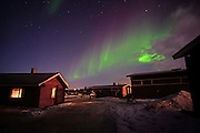 Aurora Borealis (Northern Lights) over VisitInari wood cabins in Lake Inari, Lapland, Finland