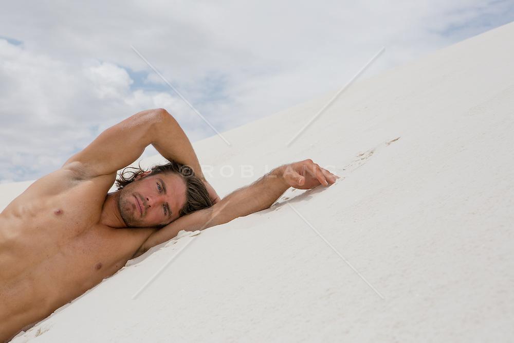 hot shirtless man on a sand dune