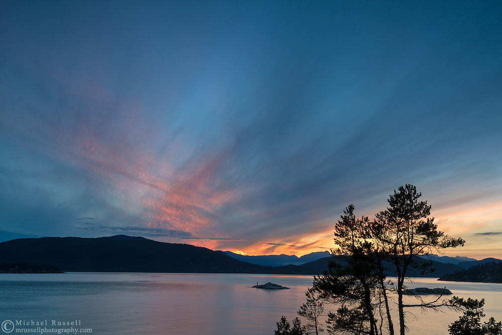 Sunset view of Howe Sound from Juniper Point at Lighthouse Park in West Vancouver, British Columbia, Canada. In the background you can see the Grebe Islets, Bowen Island, and the mountain peaks in the Sunshine Coast's Tetrahedron Range.