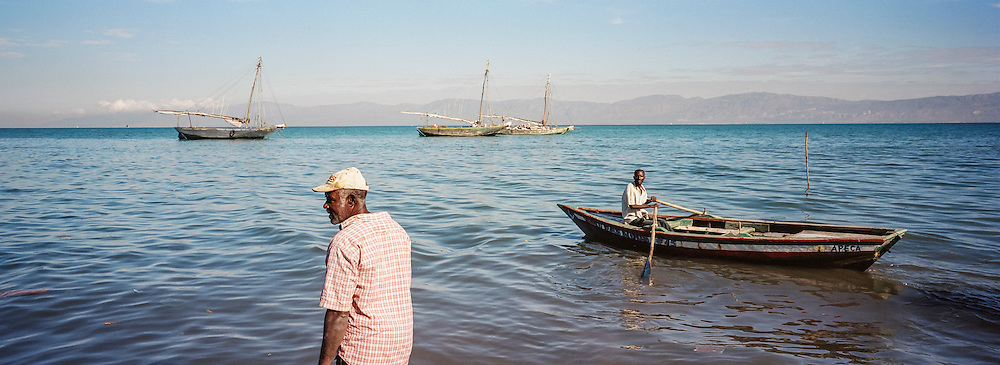 Fishermen Jean Claude Pierre, foreground, and Jean Claude Joseph, rowing the boat in back, pull in a net to check their catch on Monday, December 15, 2014 in Port-au-Prince, Haiti.